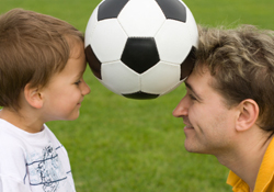 A soccer ball is balanced precariously betwixt the foreheads of a wee lad and his coach.